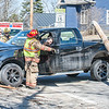 Lewiston firefighter Lt. Dave Beaule opens the door for the driver of a pickup that hit a utility pole on Farwell Street in Lewiston Monday afternoon.  The uninjured man wisely stayed in his vehicle with his dog until CMP arrived and cut the power. (Russ Dillingham/Sun Journal)