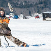Owen Cruz, 11, of Auburn, catches a frozen fish that his brother Cody threw on Sabattus Lake Saturday afternoon while they wait for flags to go up during the 2nd annual Oak Hill Boosters Pike Derby.   (Russ Dillingham/Sun Journal)