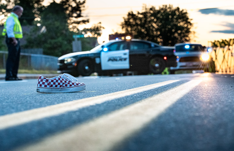 One of two sneakers of a young boy hit by a car at the corner of Dow Avenue and Sabattus Streets in Lewiston remains in the middle of the street as Lewiston Police Detective Tom Murphy works with an accident reconstruction team Monday at sunset. The setting sun is often blinding to drivers and pedestrians on this stretch of road, especially at this time of year.