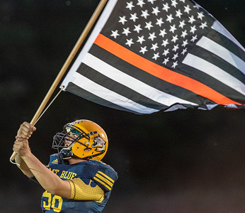 Mt. Blue football player John Howard waves a special American flag in honor of the victims of Monday's explosion in Farmintgon as the Cougars take the field Friday night for their game against Brewer.