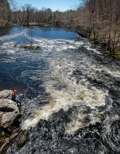 """Ryan Hanson, of Lewiston, tries his luck on the Little Androscoggin River in Minot Tuesday afternoon.  """"This is my go-to spot and I figured what better way to practice social distancing on my day off than to be here."""" said Hanson as he swapped tackle."""