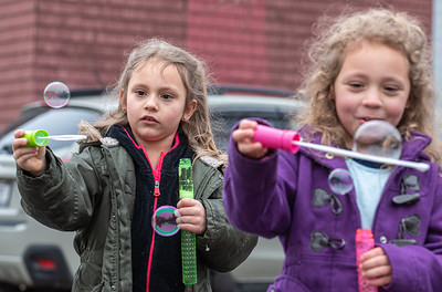 """Sisters River, left and Rowan Flynn blow bubbles next to their home on Taylor Street in Auburn Friday morning.  """"We have been cooped up inside since school closed and today was the first day we have been able to get outside.  My kids have an autoimmune disease so I have not dared let them out, but today is a damp and drizzly day so there is nobody outside and they really need to get out.  There are usually a lot of kids in the neighborhood that all come over and play but it's too dangerous as they don't understand about keeping their distance."""" said Hayley, their mom."""