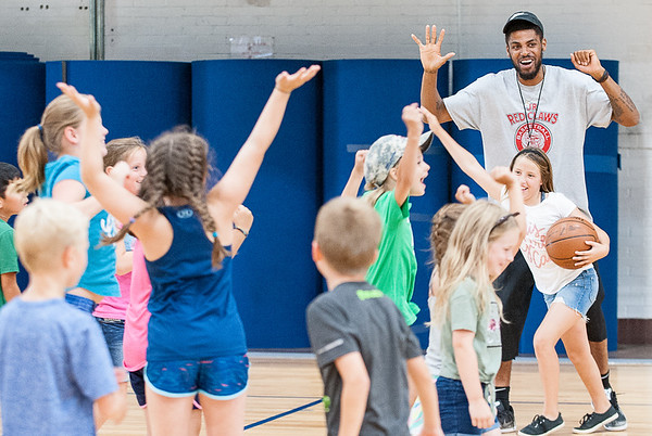 Former Maine Red Claws player Malcolm Miller reacts with area kids during a drill Monday morning at the Lewiston Armory.  He and other former players, volunteers and coaches were conducting the annual Maine Red Claws Summer Clinic sponsored by Dunkin' Donuts that is free for 7-14 year olds.  Lewiston was the first of 5 one day clinics throughout the state that aims to bring excitement for professional basketball and teach skills to young kids. (Russ Dillingham/Sun Journal)
