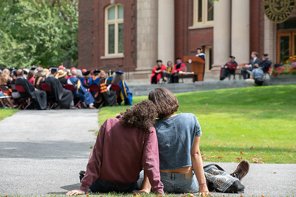 A young couple watches Tuesday's Opening Convocation in the school's quad