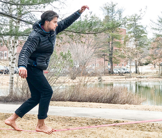 Kawai Marin, a senior at Bates College in Lewiston, takes his mind off finals Wednesday morning by slacklining next to the school's pond where the ice recently sank and the ducks begin to return.  (Russ Dillingham/Sun Journal)