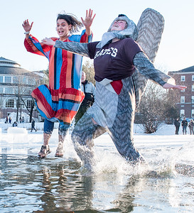 "Bates College sophomores Anna Maheu, left and Malie White jump into Lake Andrews during Friday afternoon's annual ""Puddle Jump"" on the campus of Bates College in Lewiston, Maine on February 8, 2019.  Visit sunjournal.com to watch a video of the event. (Sun Journal photo by Russ Dillingham)"