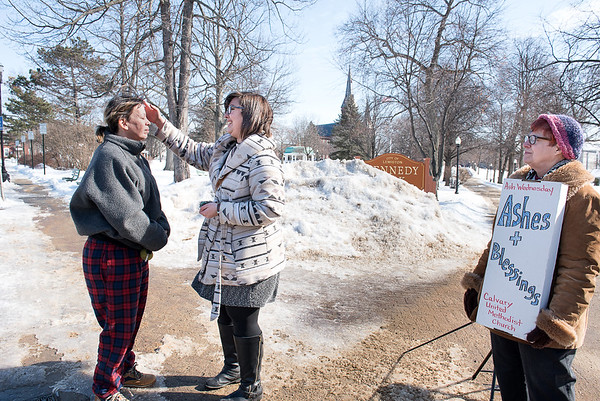 Calvary United Methodist Church of Auburn, Maine pastor Annie Baker-Streevy, center, administers ashes to the forehead of Lewiston resident Stardust Chase in Kennedy Park in Lewiston, Maine Wednesday afternoon, February 13, 2018.  At right is inner faith chaplain Pat Hunter-Gardiner.  Their objective was to bring their message to people who may have been too busy to go to church on Ash Wednesday and at the same time give out Valentines Day cards.  (Russ Dillingham/Sun Journal)