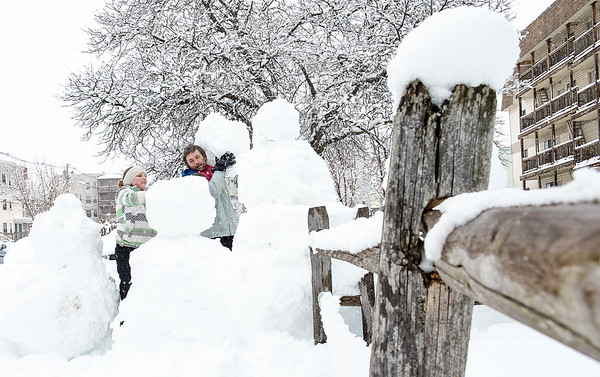 Instead of just shoveling the snow over the fence in front of their apartment on Maple Street in Lewiston, Manis Herrmann, 10, and her father Michael chose to be creative and make a family of snowmen on Wednesday morning.  (Russ Dillingham/Sun Journal)