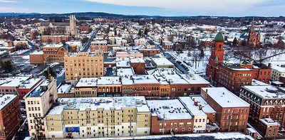 The Hartley Block, lower left, will soon fill a giant void in the landscape of Lisbon Street in Lewiston, Maine where developers welcomed visitors to a sneak peak of a few of the 1, 2 and 3 bedroom apartments that were finished.  In addition to the score of apartments, the first floor will be available for retail stores.  (Sun Journal aerial photo by Russ Dillingham)