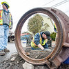Donald Harrington, left, a flagger from Complete Labor & Staffing, looks for cars to stop on Summer Street in Lewiston as Troy Ouellette, from Morin Excavation applies mortar to a man hole Tuesday afternoon. In the past year Ouellette has built up over 500 in local streets scheduled to be paved, or in this case, have it's final coat of pavement applied after paving stopped for the winter. State and municipal paving projects will ramp up again as plants that make the tar come back online throughout the Northeast.  (Russ Dillingham/Sun Journal)