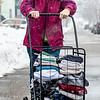 """Cheryl MacDonald squints and grits her teeth as a cold wind blows snow into her face as she walks down Horton Street in Lewiston Monday afternoon after coming from a local laundromat as the latest snowstorm whips up. """"After living in Maine long enough, you get used to this and it's actually very pretty, but I can't wait for warmer weather."""" she said while turning the corner and heading for her apartment another block away."""