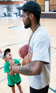 Former Maine Red Claws player Malcolm Miller talks with Emma Randall, 6 Monday morning at the Lewiston Armory.  He and other former players, volunteers and coaches were conducting the annual Maine Red Claws Summer Clinic sponsored by Dunkin' Donuts that is free for 7-14 year olds.  Lewiston was the first of 5 one day clinics throughout the state that aims to bring excitement for professional basketball and teach skills to young kids. (Russ Dillingham/Sun Journal)