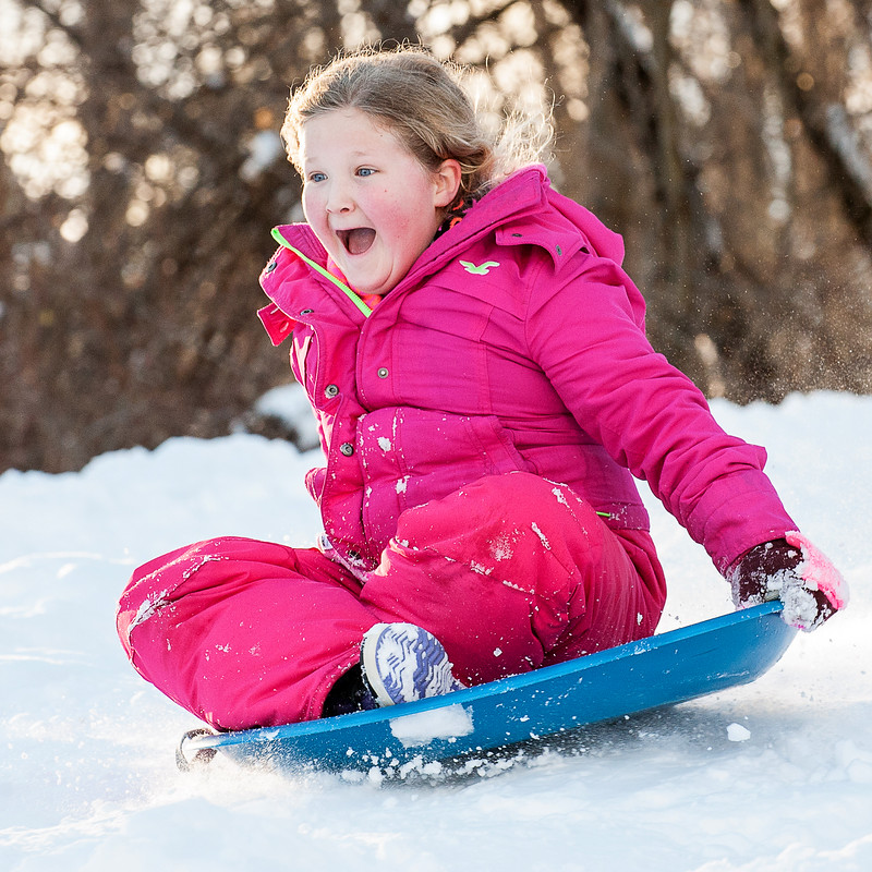 Hannah Jones, 9, of Auburn, screams with joy as she flies down the hill at Pettengill Park in Auburn Sunday afternoon as they frolicked in the nearly two feet of new snow with family and friends under bright blue skies, bright sun and warm temperatures.