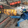 Lewiston Pulbic Works employees Dana Drew, right and Steve Damien wrestle with a wing cable as they pull it out to attach to one of the cities snowplows Tuesday afternoon in the public works garage on Adams Avenue.  They were making the preparing for a storm moving in Wednesday afternoon that is predicted to dump over a foot of snow in the area. (Russ Dillingham/Sun Journal)