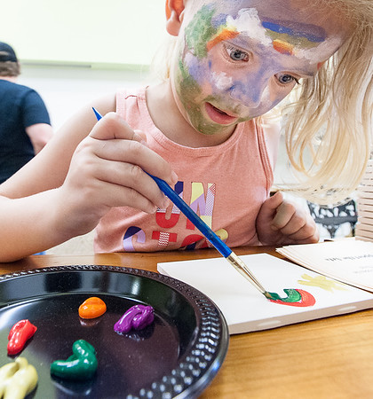 Azilee Hollenbeck, 6, of Lewiston paints a rainbow on a tile to match her face painting at one of over a dozen venues on Lisbon Street in Lewiston Friday night during the monthly Art Walk LA where thunderstorms forced all outdoor activities inside.  For more information on upcoming Art Walks, visit laarts.org  (Russ Dillingham/Sun Journal)