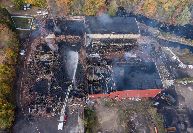 An aerial view Monday morning October 15, 2018 shows the fire scene in Mechanic Falls where a massive fire destroyed a historic mill. The complex served several businesses, including as a warehouse for Maine Cycle, and was filled with motorcycles and parts. Corcoran Environmental Services, which recycles plastics, also operated at the mill. According to Zachary Maher, town manager in Mechanic Falls, the building is owned by Charles Starbird.  (Russ Dillingham/Sun Journal Aerial)