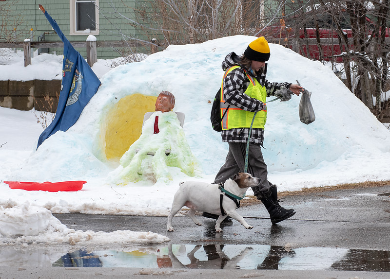 """Anna Pair walks her dog Toby back to her house after taking him outside for his afternoon business Wednesday on Lake Auburn Avenue in Auburn, Maine January 1, 2020.  In the background is a snow igloo she and her family made duing Christmas vacation that she said was the best vacation ever.  Her husband made the Donald Trump snowman to """"get under the skin of some of the neighbors"""" Pair said.  While they are on the fence about supporting Trump, they like the conversation piece where they hope to engage in civil discourse in what Pair feels is a toxic political environment."""