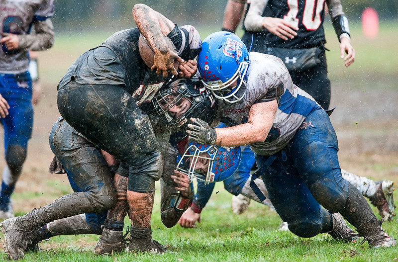 Oak Hill High School's James Borkowski, Jr., right, and Gavin Rawstron, bottom, tackle Lisbon's Lucas Francis during Saturday playoff football game in Lisbon on October 27, 2018 in Lisbon, Maine. (Russ Dillingham/Sun Journal)
