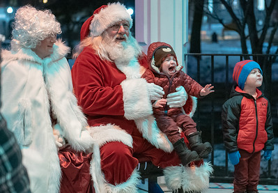 Harrison Cooper, of Auburn, Maine is all smiles while having a free photo taken with Santa and Mrs. Claus in the gazebo at Kennedy Park in Lewiston, Maine on Friday night November 6, 2019 during the annual Twin Cities Holiday Celebration.  His brother, Roman Cooper was not thrilled.