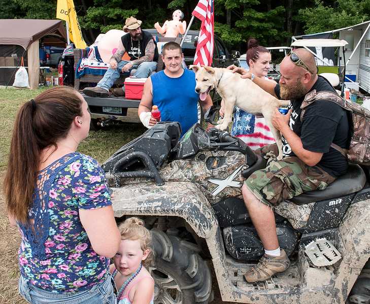 Jake Strait, of Gardner, Massachussetts gives his friend's dog Beast a ride on his ATV at 2018 Redneck Games in Hebron Friday afternoon.  The gathering is expected to draw over 5,000 people over the weekend with bands, unique competitions and hanging out with friends.  Strait is surrounded by friends from Livermore who he had an accident with last year but bonded with during the festivities. Visit sunjournal.com to watch a video from Friday afternoon. (Russ Dillingham/Sun Journal)