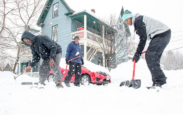 """With reports of 16 inches of wet snow from another Nor'easter overnight, Brian Morency, left, dropped his shovel to hammer loose the packed snow in the driveway of his apartment on Winter Street  in Lewiston Wednesday morning.  His landlord Brett Williams, center, and his son Jeremiah, were shoveling.  """"Thought we were over this."""" said Brett as he scooped another shovel full of the heavy snow.  (Russ Dillingham/Sun Journal)"""