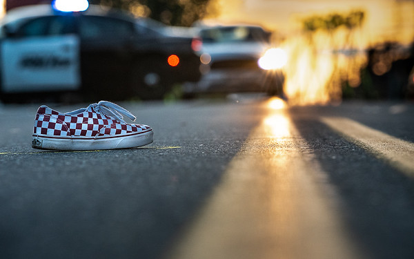 One of two sneakers of a young boy hit by a car at the corner of Dow Avenue and Sabattus Streets in Lewiston remains in the middle of the street as Lewiston's accident reconstruction team works the scene Monday at sunset. The setting sun is often blinding to drivers and pedestrians on this stretch of road, especially at this time of year.