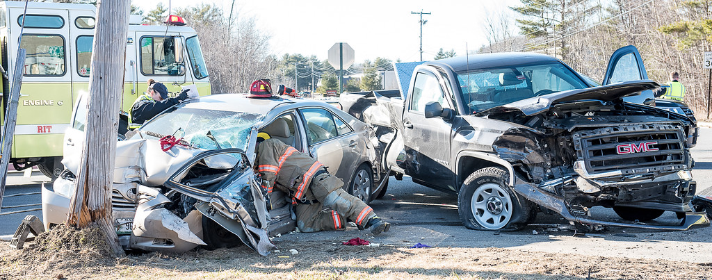 A Lewiston firefighter leans into a vehicle involved in an accident at the corner of Westminster Street and Lexington Street in Lewiston Thursday afternoon.  The driver of the sedan, left was trapped in the vehicle and had to be extricated by firefighters.  The driver of the pickup walked away but multiple occupants of the sedan were taken to the hospital.  (Russ Dillingham/Sun Journal)