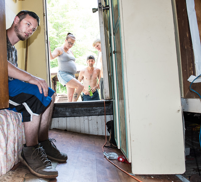 Brock Benedix, left, sits outside his room at his home in Sabattus Monday afternoon where the floor broke free from the walls Sunday.  Looking on is his mother Corrie Bergeron, second from left and her husband John Bergeron and her stepson Nicholas Bergeron, right. (Russ Dillingham/Sun Journal)