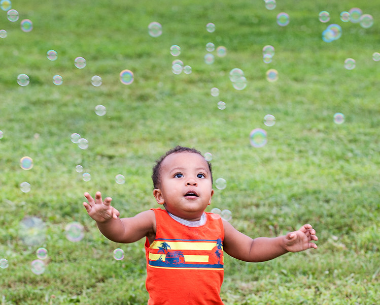 Zander Callahan, 20 mos., of Lewiston, chases bubbles his mother was making at Simard Payne Memorial Park in Lewiston Friday night as they waited to see the balloons launch.  (Russ Dillingham/Sun Journal)