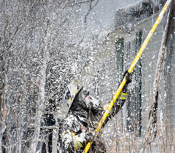 A firefighter is showered with firefighting foam as they pull apart the walls of a mobile home at 65 Bridgham Road in Buckfield Thursday morning.