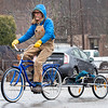Paul Swearinger, of Auburn, rides his custom built bike through a parking lot in Auburn Monday afternoon on his way to the Androscoggin River to collect driftwood to carve into pieces of art.