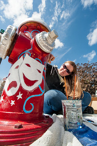 Melanie Therrien paints the fire hydrant across from the Public Theatre in Lewiston at the corner of Maple and Lisbon Streets Friday morning.  She is with a group of local artists spreading their talents across the city with murals, sidewalk art and creative cross walk themes with many more projects in the works (Russ Dillingham/Sun Journal)