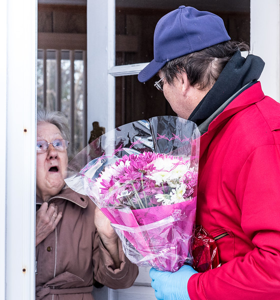 Claudette Coy reacts as she opens her front door on Lower Street in Turner Thursday morning and learns that she was receiving a free tank of oil from Murray-Heutz Oil & Propane of Turner in addition to flowers and a box of chocolates delivered by David RIchard, right.  For the fourth year in a row,  Maine Energy Marketers Association has organized the event with it's members to deliver free oil and propane to some of their loyal customers who they felt would benefit the most from the kind gesture. (Sun Journal photo by Russ Dillingham)