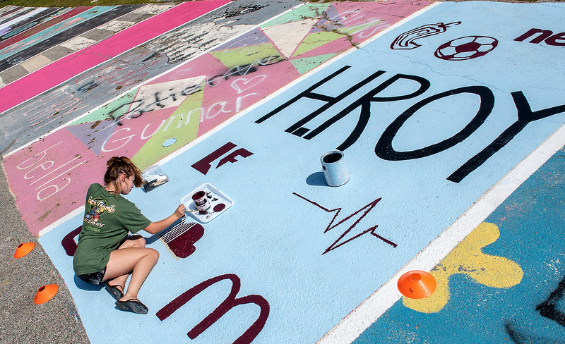 """Edward Little High School senior Hanna Roy paints her designated parking space in the lower lot at Edward Little in Auburn, Maine Thursday morning August 15, 2019.  Nobody at the school knows how long the tradition has been going on but someone who has been at the school for 20 years said it started long before she got there.  According to principal Scott Annear, there are no rules to this """"weird tradition"""" except they have to be """"appropriate"""" and is """"first come first serve"""" and unofficially begins after the lines in the parking lot are painted, which was this past Monday."""