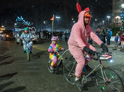 Andy Allen and his daughter Makenzie, of Auburn, ride a tandem bicycle down Main Street in Auburn, Maine during Friday night's parade during the Twin Cities Holiday Celebration.