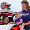 Lila White, center,from South Paris, wishes her father, Cody, good luck while being held by her mother, Courtney before heading out on the track for his race at Oxford Plains Speedway.