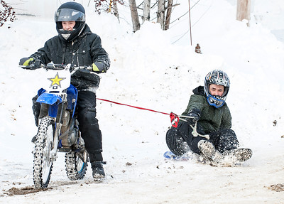 """Phillip Pendexter, 15, pulls his friend Jordan Carter, 15, around their Spring Street neighborhood in Lewiston Sunday afternoon.  """"We were watching YouTube videos of people """"sending it"""" so we decided to send it ourselves"""" (Russ Dillingham/Sun Journal)"""