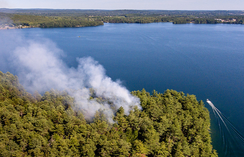 In addition to firefighters bushwacking through brush and across streams to get to a woods fire near Tabers on Lake Shore Drive in Auburn Monday afternoon, many were ferried over on boats from the Route 4 boat launch.  A helicopter making water drops was also used.
