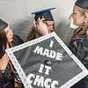 Samantha Burke, right, adjusts the tassel of Olivia Dooley, center as Samantha Martin, left, looks on as they line up in one of the halls at the Androscoggin Bank Colisee in Lewiston prior to graduating Thursday night.  (Russ Dillingham/Sun Journal)