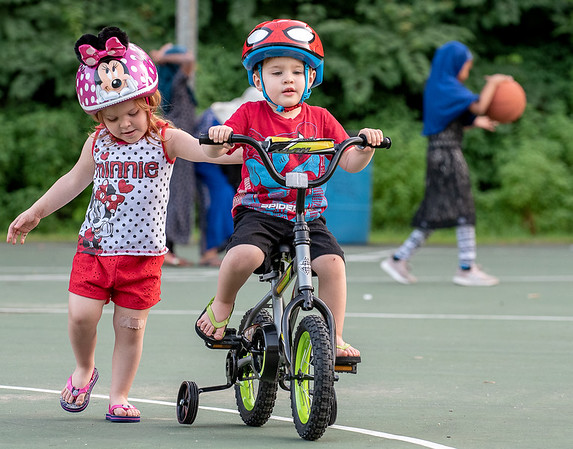 Ellenor Clavette gives her 3 year old twin brother Ayden a push as they learn to ride bicycles for the first time on their birthday presents at Union Street Gully in Auburn Thursday night.
