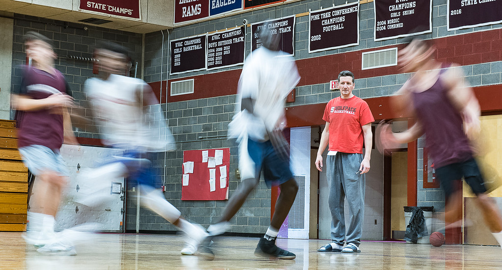 Edward Little High School basketball players are a blur as they run through a drill during Wednesday's practice at the school's gym under the watchful eye of their head coach, Mike Adams, middle, as they prepare for Friday night's state championship game in Portland against Scarborough. (Russ Dillingham/Sun Journal)