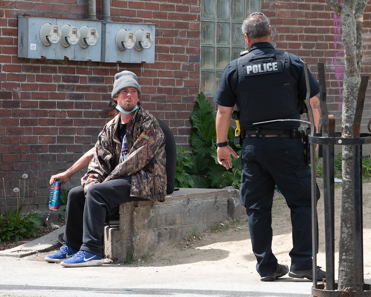 """Lewiston police officer Bill Rousseau confronts a pair of """"loiterers"""" near the corner of Walnut and Bartlett Streets in Lewiston Thursday afternoon while on patrol.  He issued a warning after the beer was dumped and they moved along.  LPD is stepping up patrols and field interviews after a recent rash of gun shots and violence in the downtown area."""