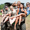 A group of friends hang off the back of an ATV as they cruise around the campgrounds at the Redneck Games in Hebron Friday afternoon.  A half dozen bands, unique games, a mud run and a wet T-shirt contest highlights the weekend activities that is expected to draw over 5,000 people of all walks of life. Visit sunjournal.com to watch a video from Friday afternoon. (Russ Dillingham/Sun Journal)