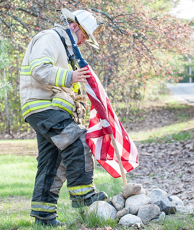 Auburn Fire Battalion Chief Dean Milligan finds a home for a flag taken down from the charred front porch of a home on 32 Snell Hill Road that was destroyed by fire Friday afternoon.  (Russ Dillingham/Sun Journal)