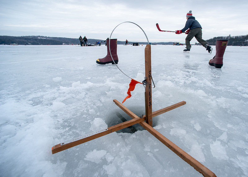 Forrest St. Laurent, of Sabattus skates after the puck while playing hockey with his friend, Jensen Page, of Leeds on Sabattus Pond in Wales while keeping an eye on their ice fishing traps during Saturday's 4th Annual Oak Hill Boosters Pike Fishing Derby.