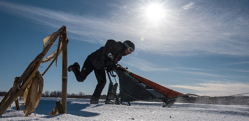 ean Rene Saucier of Woburn, Quebec pushes his sled through a frozen cornfield in Farmington, Maine in Sunday's Maine State Sled Dog 8-team Race February 17, 2019.
