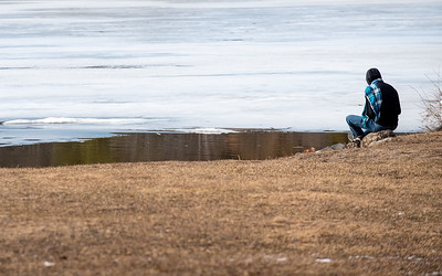 A young boy enjoys a bit of solitude along the shore of Cochnewagon Lake in Monmouth, Maine Wednesday afternoon, March 25, 2020.