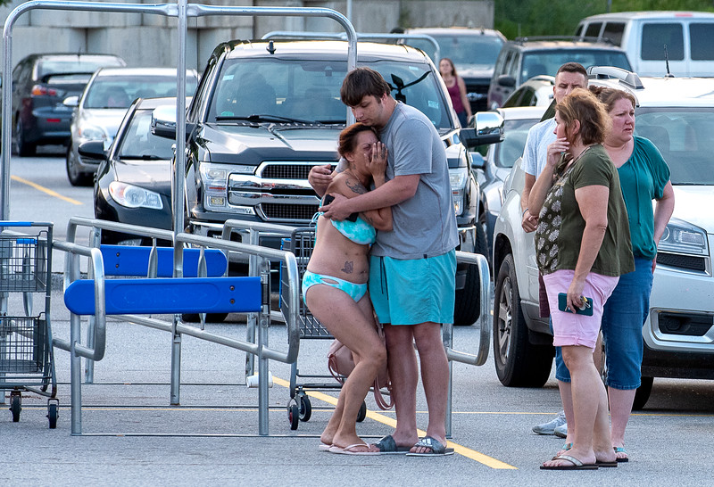 Tara Nguyen is consoled by a friend in the Auburn Walmart parking lot after her boyfriend was shot to death.