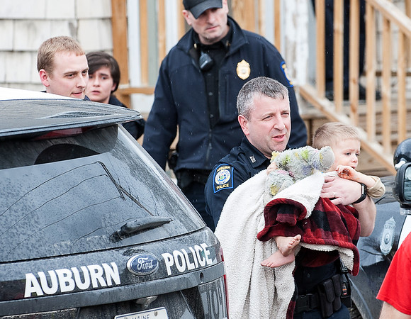 Auburn Police Officer James Davison carries a young child to a waiting rescue unit to be taken to a local hospital to be evaluated after they fell from out of a second story window at 487 Court Street in Auburn Friday afternoon.  (Russ Dillingham/Sun Journal)