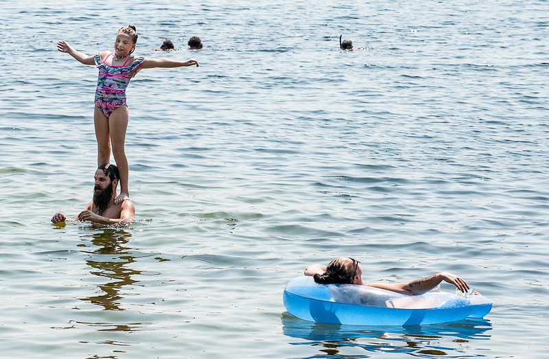 Kayci Cass, right, soaks up the sun while floating in Middle Range Pond in Poland Monday morning as her daughter Cydney, 10, jumps off her father Patrick's shoulders. The family from Auburn often come to the small roadside access point off Schellinger Road, one of the few free places left to park and access a local body of water. (Russ Dillingham/Sun Journal)